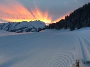 Lever de soleil sur la dameuse et les pistes de ski de fond.